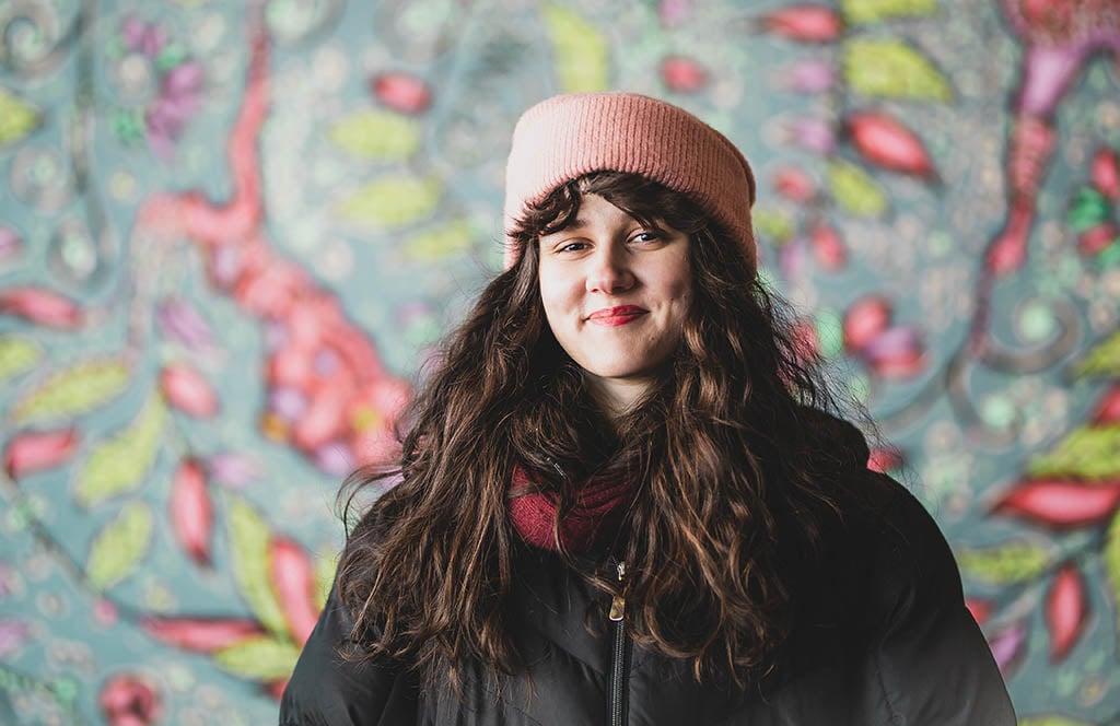 Brigita Krasniqi i stor ljusröd mössa och vinterrock ler med en brokig väggmålning i bakgrunden.