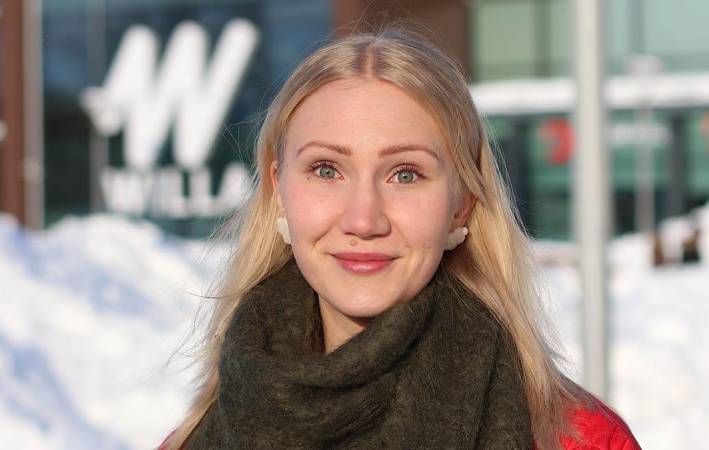 Pinja Perholehto ler i vintrig bild med affärshus i bakgrunden.